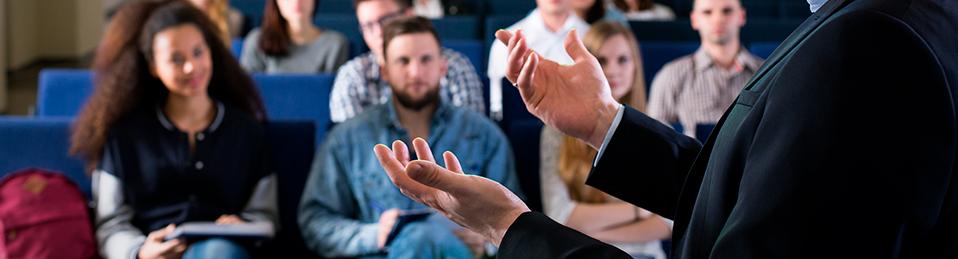 Ponente en una conferencia mientras estudiantes le atienden