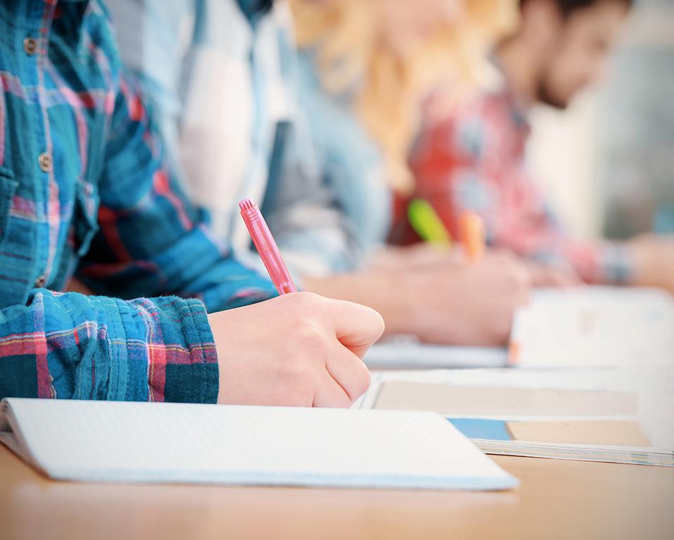 Estudiantes escribiendo apuntes mientras leen un libro