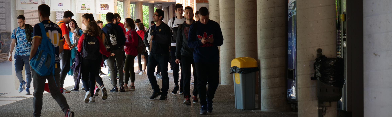 Estudiantes de la Facultad de Ciencias del Deporte caminando por zonas exteriores techadas entre edificios.
