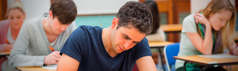 Varios estudiantes realizan un examen de manera individual sentados en sus respectivos pupitres